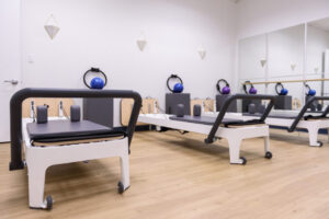 Pilates reformer machine text pilates classes at Anchor Wellness Center to another level! Sign up Now!