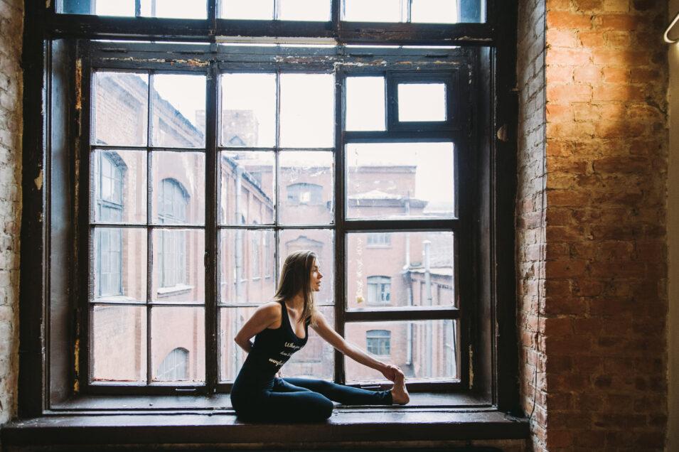 Woman Stretching Beside Big Window