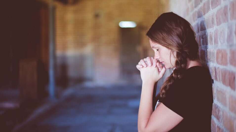 A women leaning against a brick wall praying into her hands