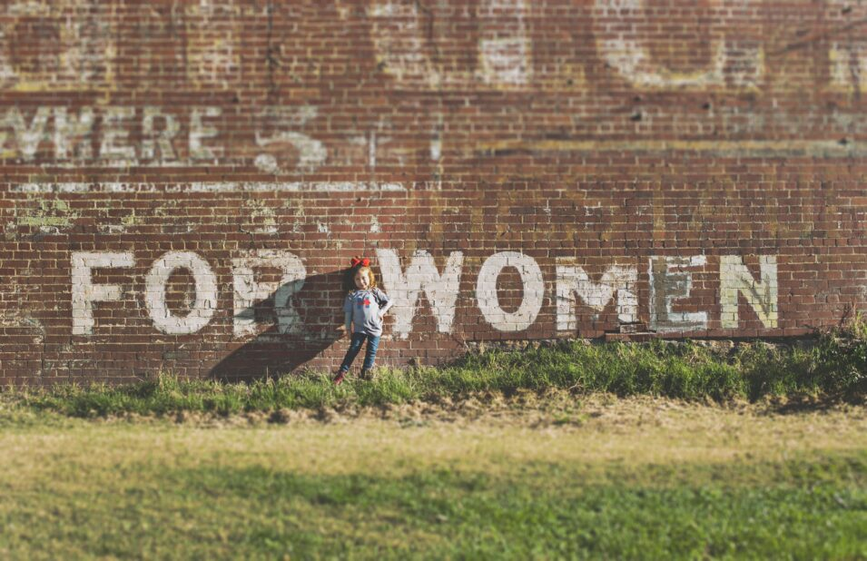 FOR WOMEN spray painted to a brick wall with a little girl standing between the words hand on her hip